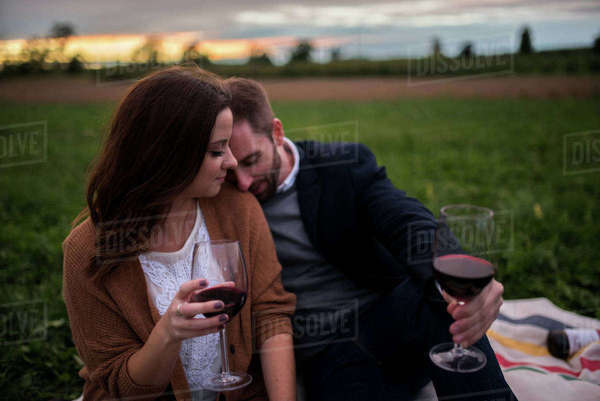 Romantic couple with red wine relaxing on picnic blanket in field at sunset Royalty-free stock photo