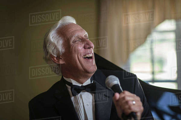 Senior man in bow tie singing into microphone Royalty-free stock photo