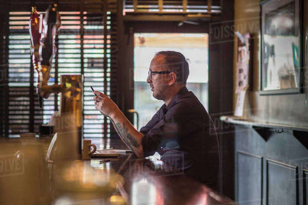 Barman reading smartphone texts at public house counter Royalty-free stock photo