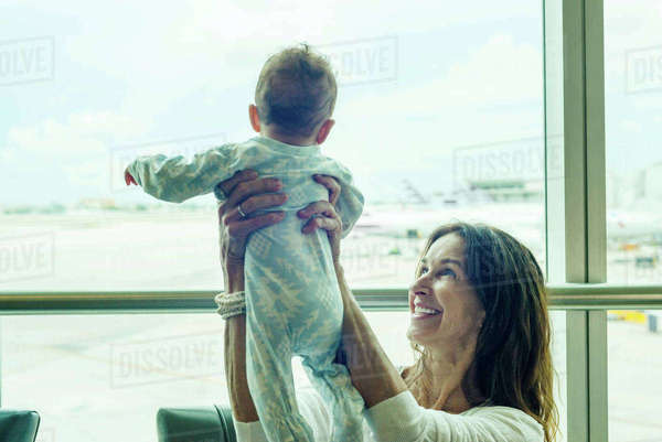 Grandmother lifting baby in mid air at airport Royalty-free stock photo