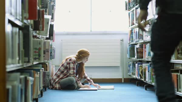 Female student studying on floor in library and man picking up book Royalty-free stock video