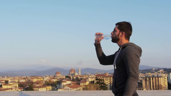 MS Man drinking water on rooftop and cityscape in background Royalty-free stock video