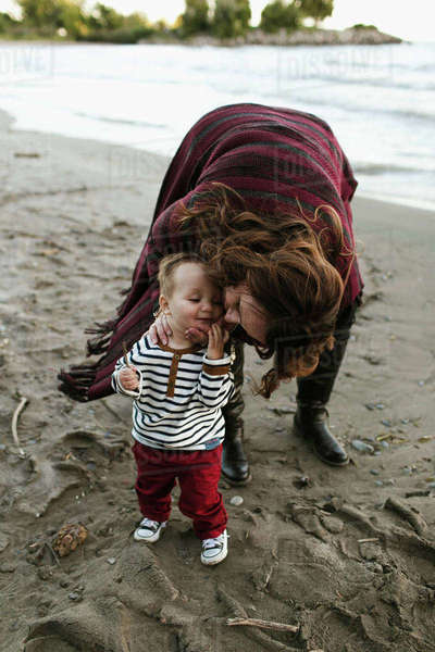 Mother on beach kissing baby boy on cheek, Toronto, Ontario, Canada Royalty-free stock photo