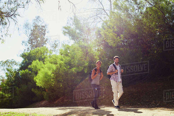 Mid adult couple hiking, walking along sunlit rural road Royalty-free stock photo