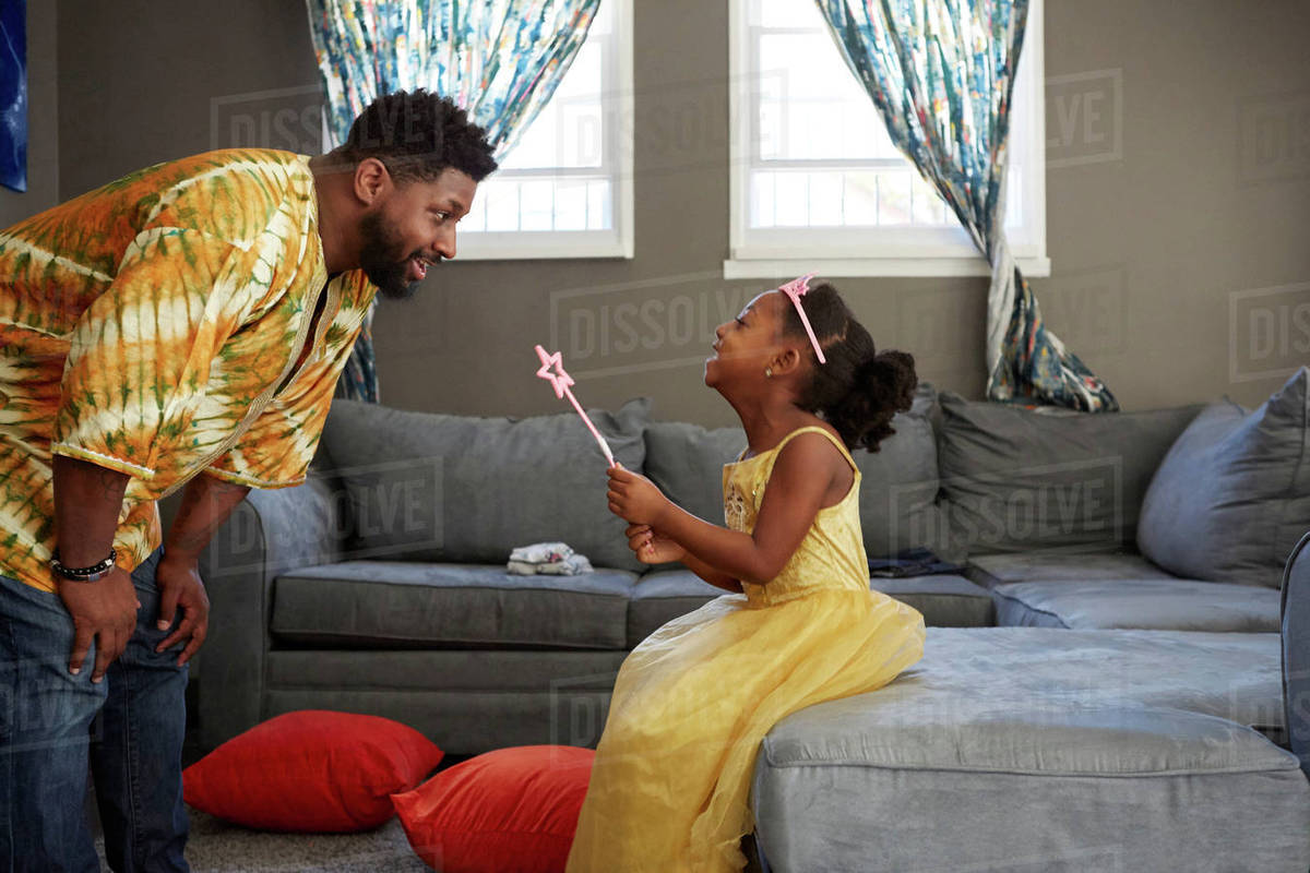 Man playing with daughter in fairy costume in living room Royalty-free stock photo