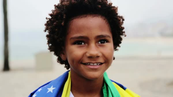 Boy (8-9) wrapped in Brazilian flag at Ipanema beach Royalty-free stock video