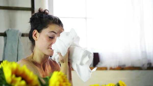Young woman drying face with towel in bathroom with sunflowers Royalty-free stock video
