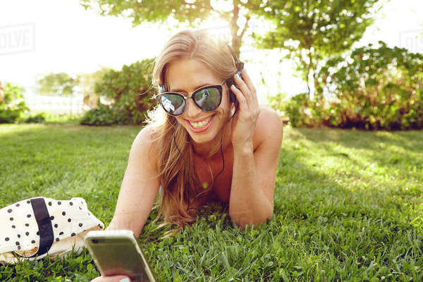 Young woman lying in sunlit park listening to smartphone music Royalty-free stock photo