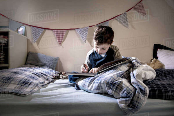 Boy sitting in bed reading book by torchlight Royalty-free stock photo