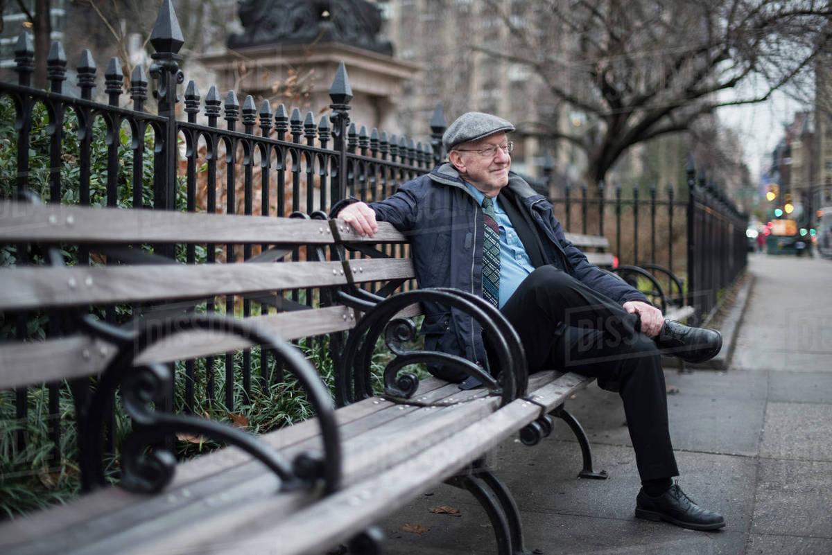 Man Sitting On Park Bench Smiling Manhattan New York Usa Stock
