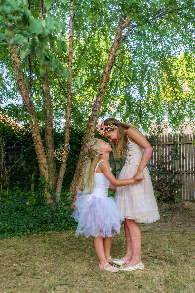 Two young girls dressed as fairies, holding hands, face to face Royalty-free stock photo