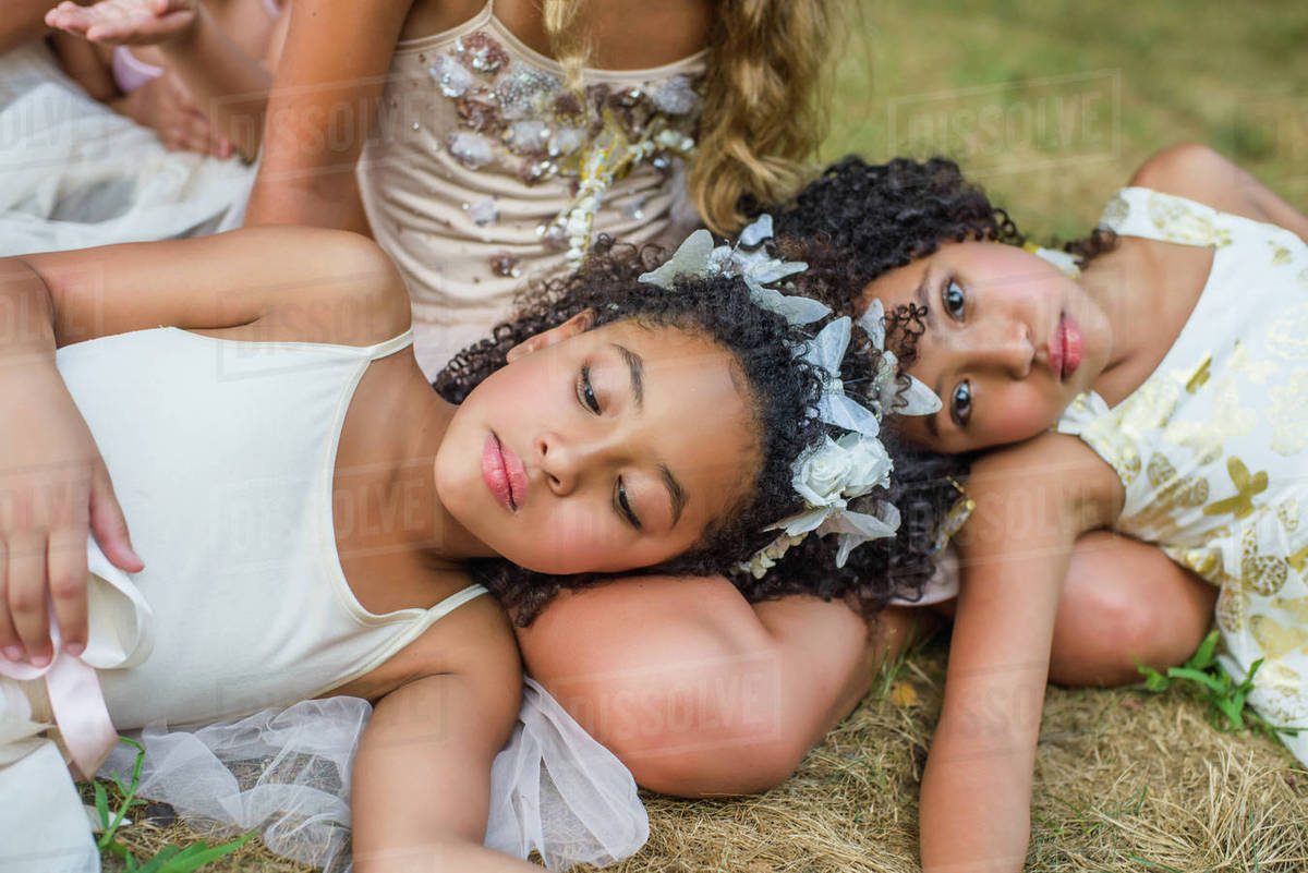 Group of young girls, dressed as fairies, lying on grass Royalty-free stock photo