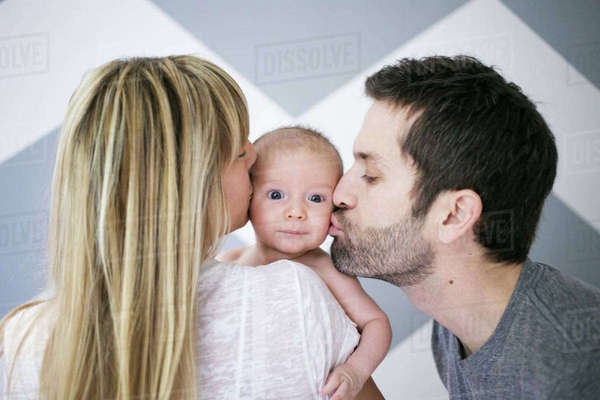 Over shoulder view of mid adult couple kissing baby son on cheek Royalty-free stock photo
