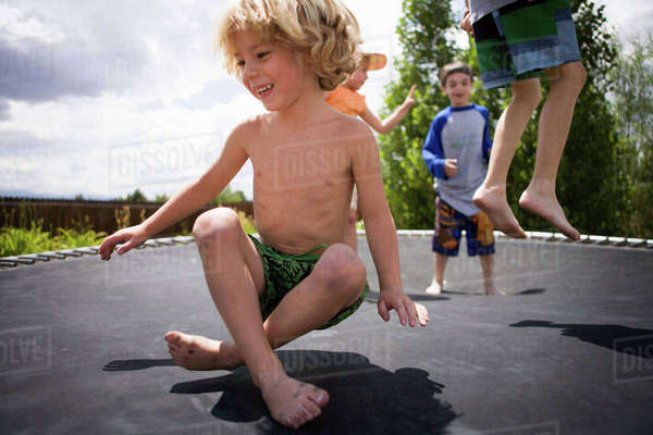 Boys jumping on trampoline outdoors Royalty-free stock photo