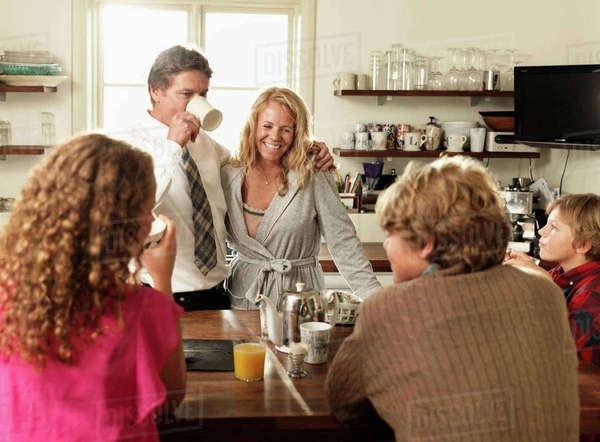 Family sitting together at kitchen table over breakfast Royalty-free stock photo