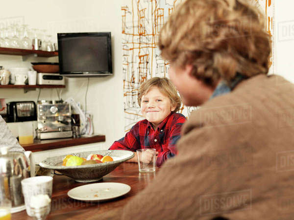 Teenage boy and brother sitting at kitchen table Royalty-free stock photo