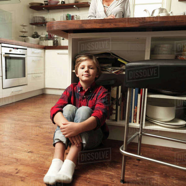 Portrait of boy sitting on floor in kitchen Royalty-free stock photo