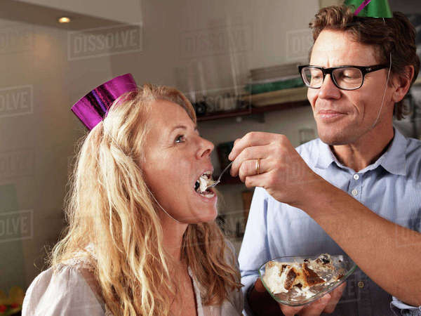 Mature man feeding cake to wife Royalty-free stock photo
