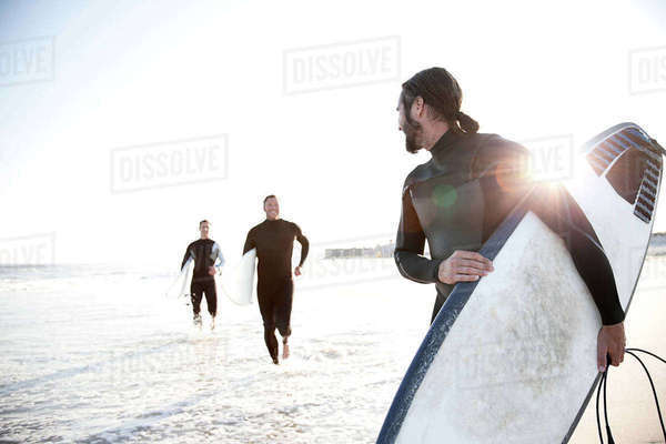 Three surfers at beach Royalty-free stock photo