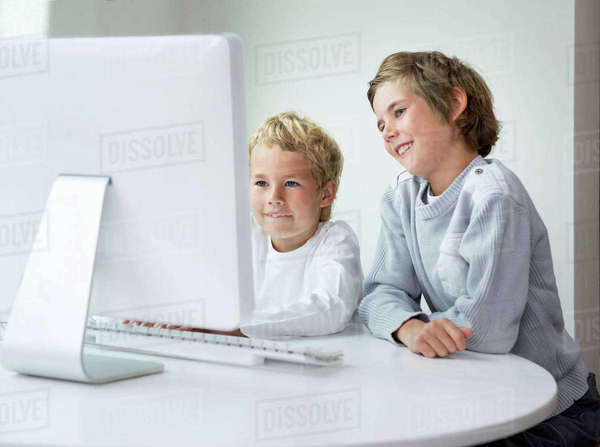 Brothers looking at computer screen Royalty-free stock photo