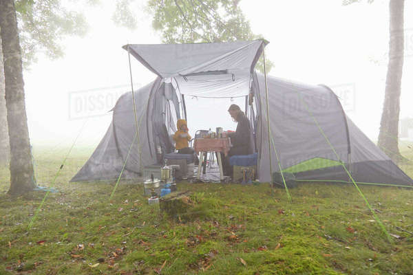 Mother and sons having breakfast in tent in misty landscape Royalty-free stock photo