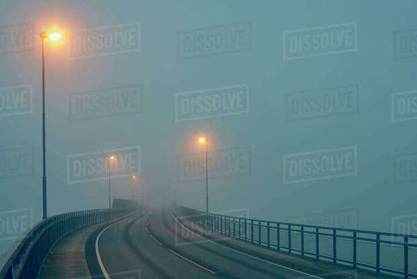 Diminishing perspective of misty road illuminated by street lights, Haugesund, Rogaland County, Norway Royalty-free stock photo
