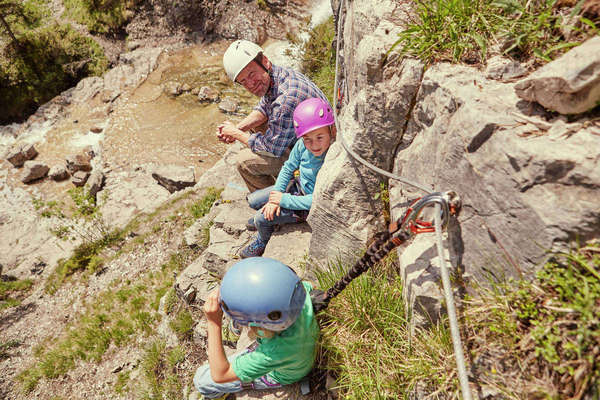 Father and children enjoying view on rocks, Ehrwald, Tyrol, Austria Royalty-free stock photo