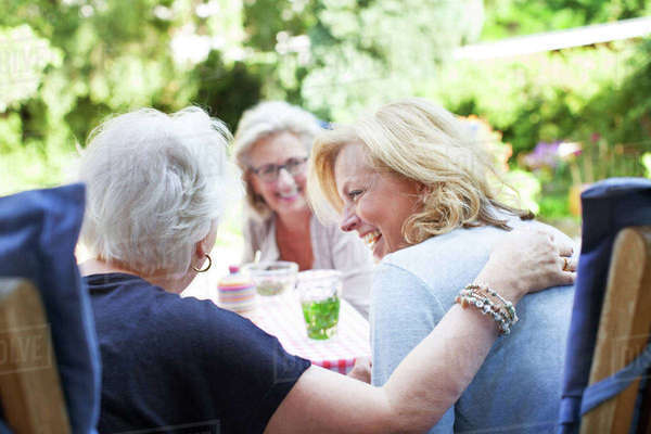 Three women relaxing together in garden, laughing Royalty-free stock photo