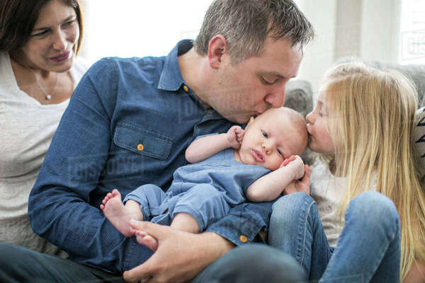 Family sitting on sofa, father and young girl kissing baby boy Royalty-free stock photo