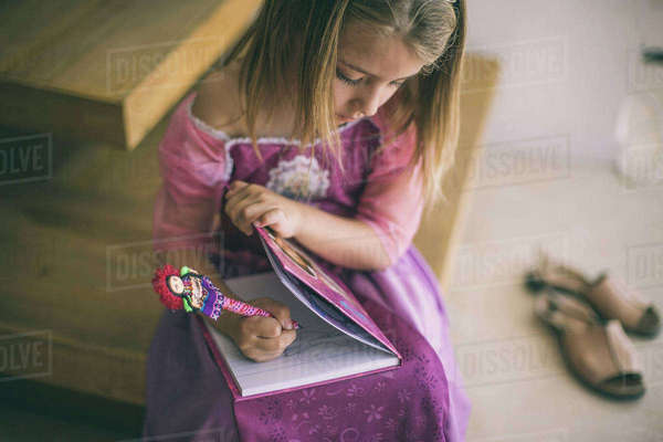 Young girl wearing princess dress, sitting on stairs, writing in book Royalty-free stock photo