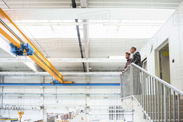 Supervisor and manager looking out from top of distribution warehouse stairway Royalty-free stock photo