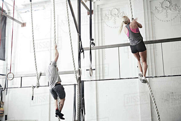 Couple rope climbing in cross training gym Royalty-free stock photo