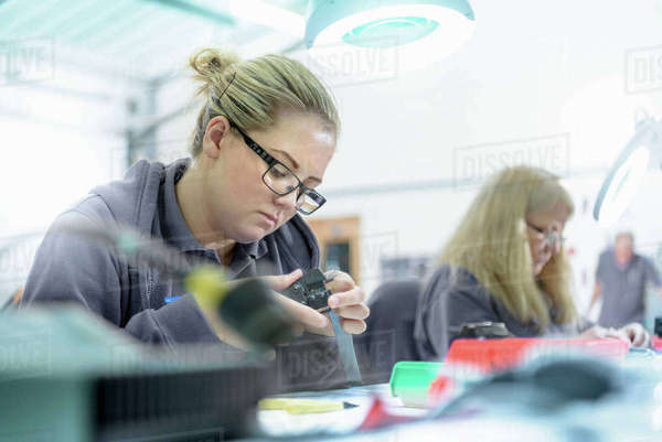 Female apprentice electrical engineers in cable finishing factory Royalty-free stock photo