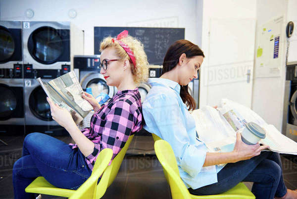 Two women reading newspapers back to back in laundrette Royalty-free stock photo