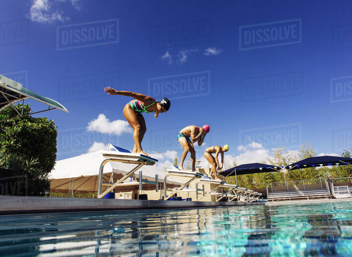 Swimmers on pool diving board stock photo