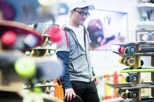 Young male skateboarder looking at skateboards in skateboard shop Royalty-free stock photo