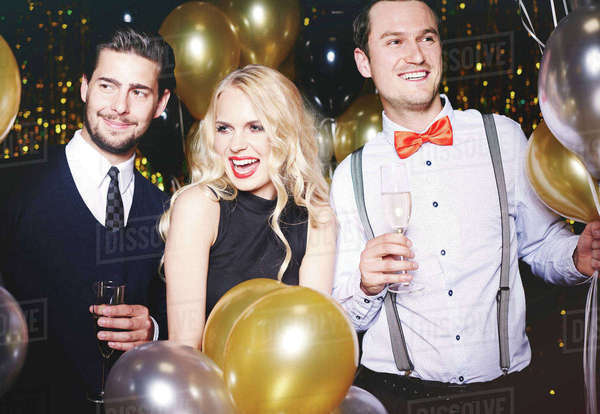 Portrait of three people at party, surrounded by balloons, holding champagne glasses Royalty-free stock photo