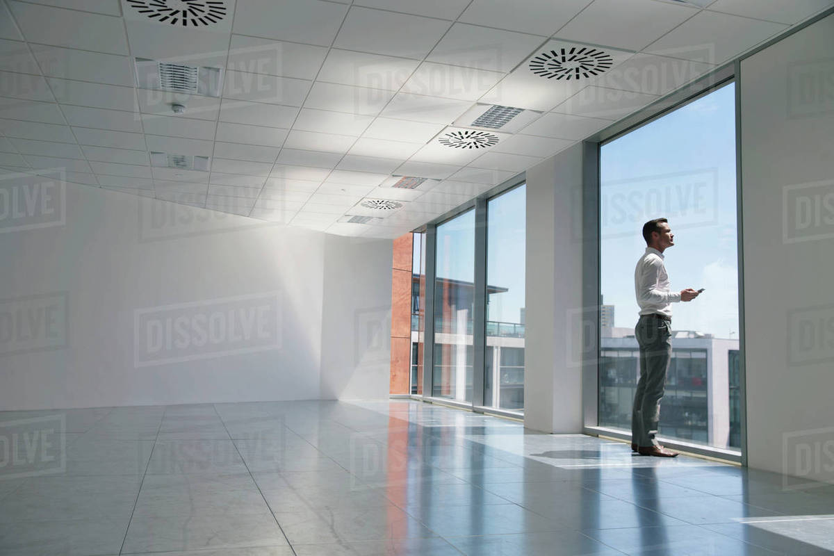 free office space. Businessman Looking Out Of Window, In Empty Office Space Free R
