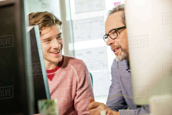 Male digital designer explaining design to trainee at office desk Royalty-free stock photo