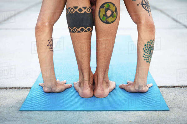 Rear view of man practicing yoga, standing on yoga mat with hands on floor Royalty-free stock photo