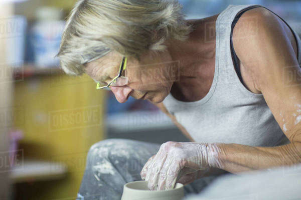Senior woman in pottery workshop, at potters wheel, making bowl, close-up Royalty-free stock photo
