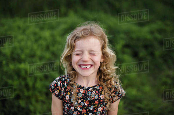 Portrait of girl with wavy blond hair and missing tooth in field Royalty-free stock photo