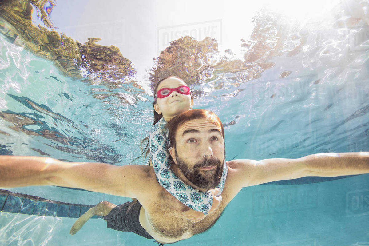 Underwater view of mature man swimming with daughter on piggy back