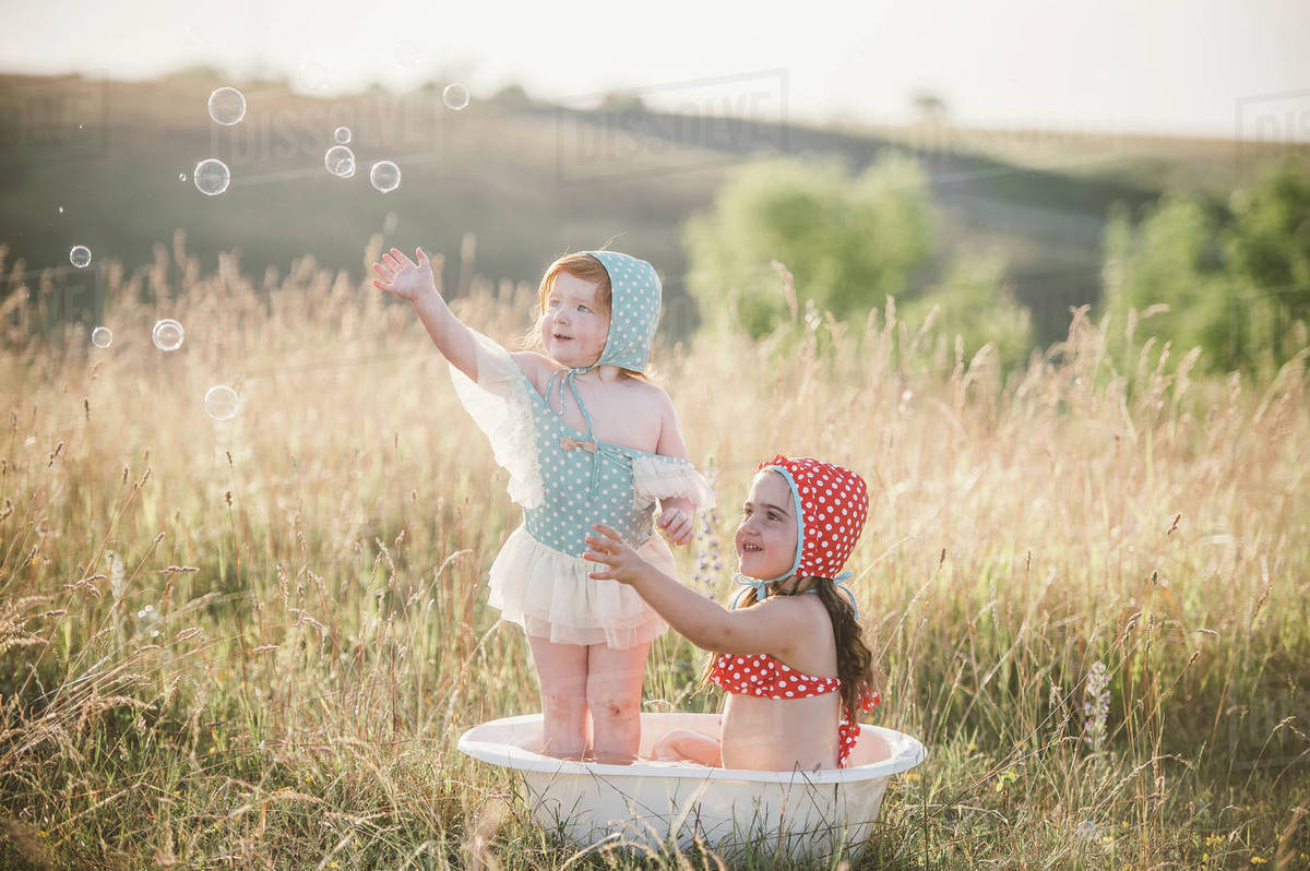 Two girls in field, playing in plastic tub of water - Stock Photo ...