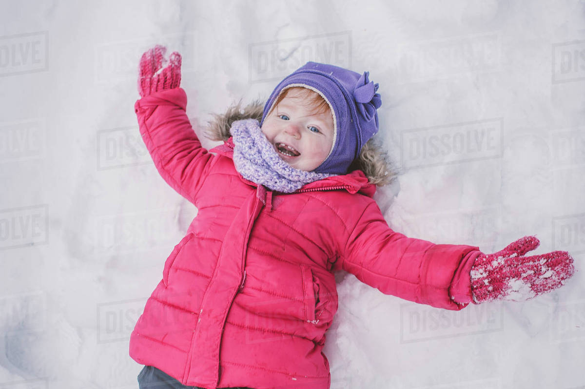 Young Girl Making Snow Angel In Snow Close Up Stock Photo