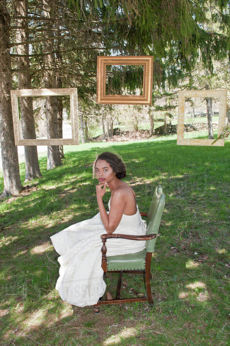 Portrait Of Bride Wearing Wedding Dress Sitting In Chair Outdoors