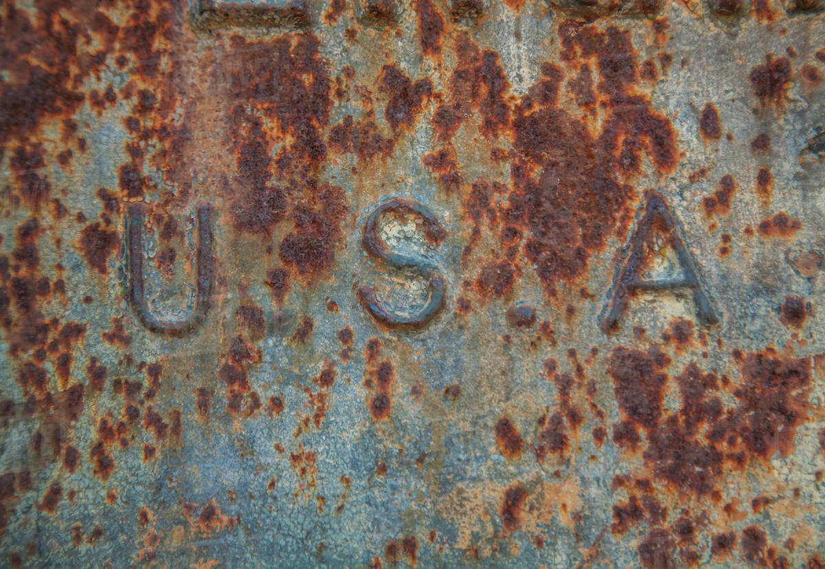 The side of a rusty iron container showing the letters USA stock photo