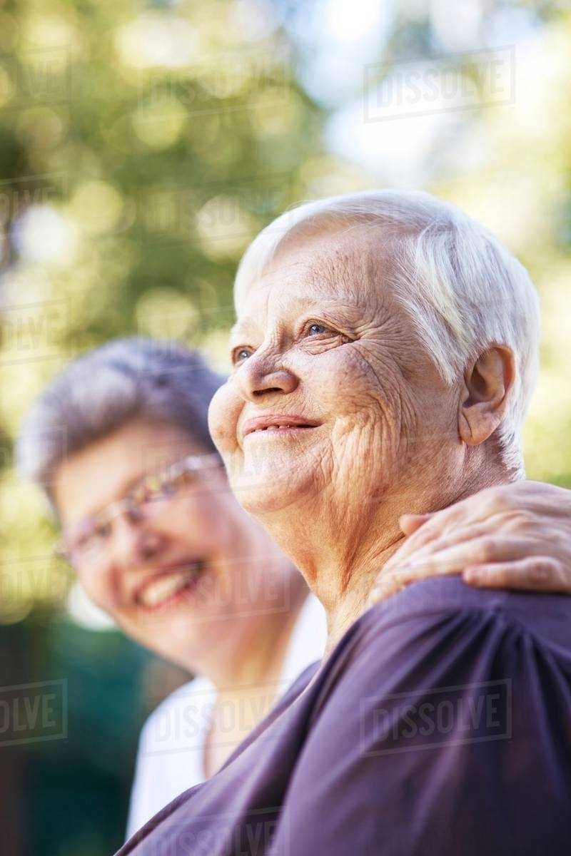 older women smiling together outdoors - stock photo - dissolve