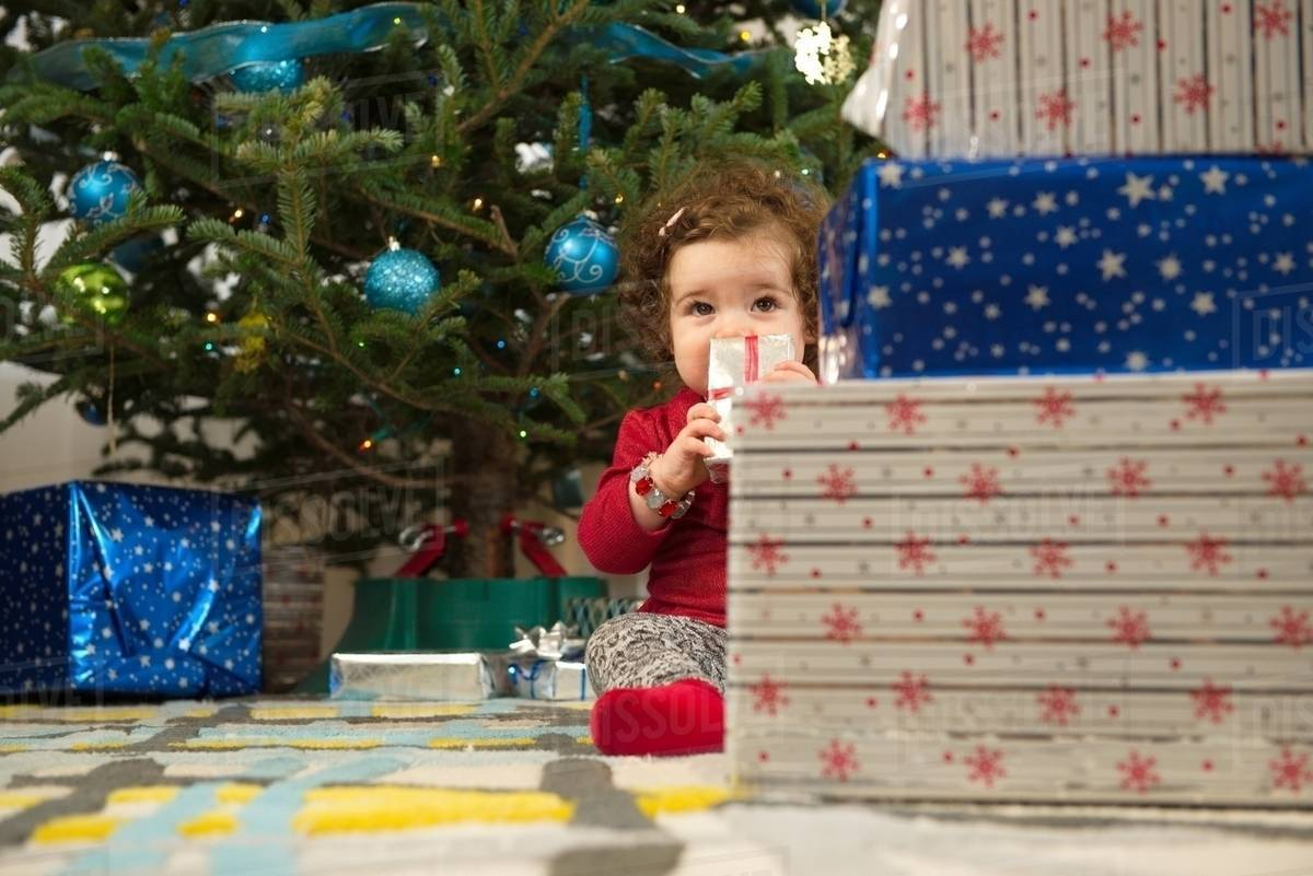 Toddler girl opening Christmas gifts - Stock Photo - Dissolve