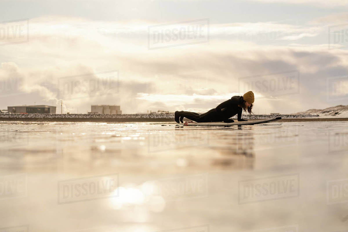 Silhouette of a woman with a surfboard lying on a beach with industrial units on the far horizon. Royalty-free stock photo